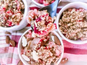 SPOON OF HEALTHY STRAWBERRY RHUBARB CRUMBLE WITH 3 BOWLS IN THE BACKGROUND